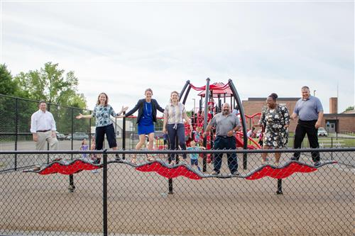 Adults standing on playground equipment