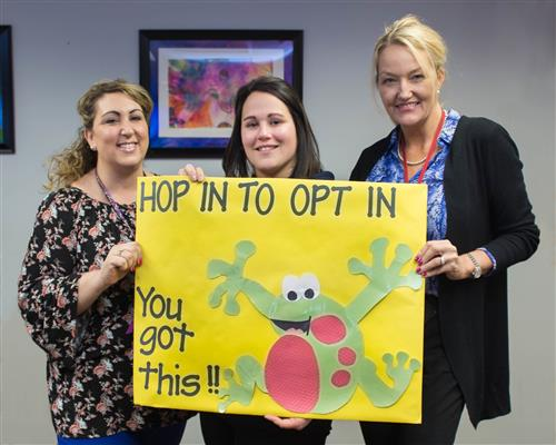 Three adults hold a 'Hop in to Opt In' sign.