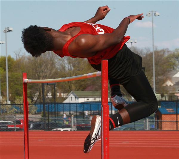 A runner jumps a hurdle